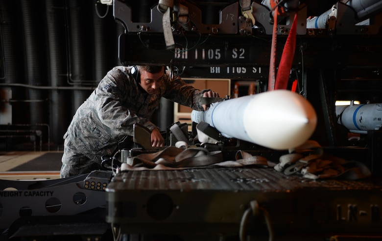 Senior Airman Leo Baum prepares to transport an Air Intercept Missile-9 during a quarterly weapons competition Oct. 31, 2014, at Royal Air Force Lakenheath, England. Load crew competitions give personnel the opportunity to display their war fighting skills and highlights the best weapons load crew for the quarter. Baum is a load crew member with the 493rd Aircraft Maintenance Unit. Members of the 493rd FS are recipients of the 2014 Raytheon Trophy, being recognized as the top fighter squadron in the Air Force. (U.S. Air Force photo/Staff Sgt. Emerson Nuñez)