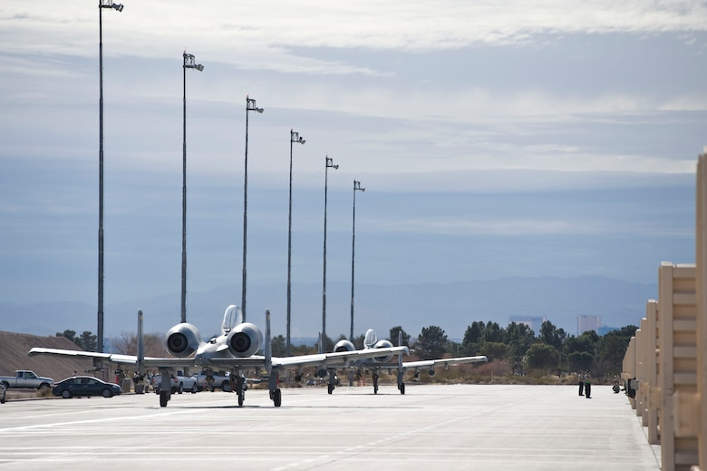Two A-10 Thunderbolt IIs assigned to the 355th Operations Group, Davis-Monthan Air Force Base, Ariz., taxi out to the flightline during Green Flag-West 15-03 at Nellis Air Force Base, Nev., Jan. 26, 2015. Students in the A-10C initial qualification program had a unique opportunity to train outside of their home-station environment, better preparing them for their first operational squadron. (U.S. Air Force photo by Airman 1st Class Mikaley Towle)