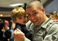FORT WAYNE AIR NATIONAL GUARD BASE, Ind. – Senior Airman Aaron Strebig, 122nd Fighter Wing, Security Forces, embraces his son as the 122nd Fighter Wing welcomed home more than two-dozen members from the 122nd Security Forces Squadron, as they returned from a six-month deployment in support of Operation Enduring Freedom, January 23, 2015 at the Fort Wayne International Airport.  Twenty-six Blacksnakes mobilized for this deployment and were assigned to the 379th Expeditionary Security Forces Squadron at Al Udeid Air Base, Qatar. The group spent one month in San Antonio conducting combat preparation, then transitioned to Qatar for six months.