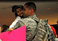 FORT WAYNE AIR NATIONAL GUARD BASE, Ind. – Senior Airman Mario Boone, 122nd Fighter Wing, Security Forces, embraces his daughter as the 122nd Fighter Wing welcomed home more than two-dozen members from the 122nd Security Forces Squadron, as they returned from a six-month deployment in support of Operation Enduring Freedom, January 23, 2015 at the Fort Wayne International Airport.  Twenty-six Blacksnakes mobilized for this deployment and were assigned to the 379th Expeditionary Security Forces Squadron at Al Udeid Air Base, Qatar. The group spent one month in San Antonio conducting combat preparation, then transitioned to Qatar for six months.