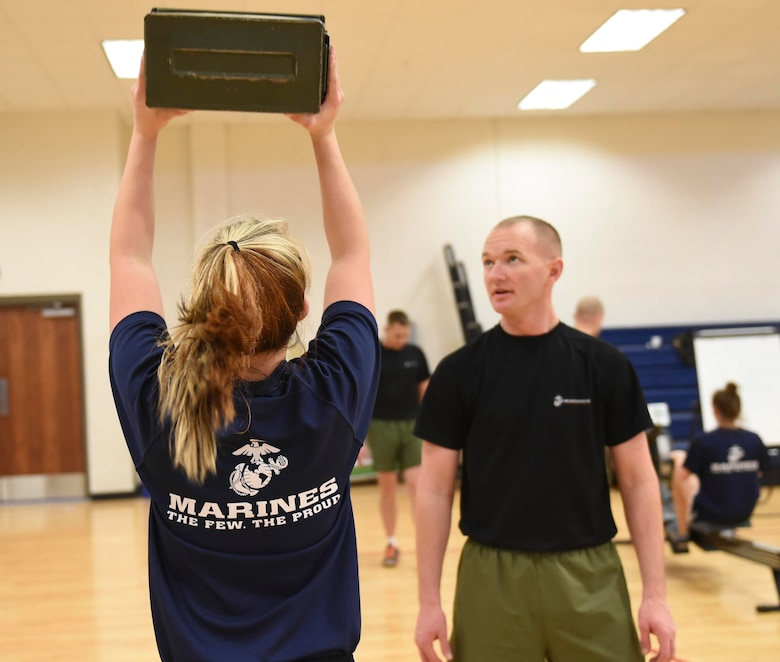 A U.S. Marine Corps poolee raises an ammunition can while a Marine looks on during a delayed entry program all-female workout held Jan. 17, 2015, at the fitness center on Buckley Air Force Base, Colo. Poolees are members of the DEP that have not yet shipped out to recruit training. The DEP workouts consist of strengthening exercises such as pull-ups, box jumps, push-ups and squats to enable the poolees to be accustomed to the vigorous workouts and stress they will endure during recruit training. (U.S. Air Force photo by Airman 1st Class Samantha Saulsbury/Released)