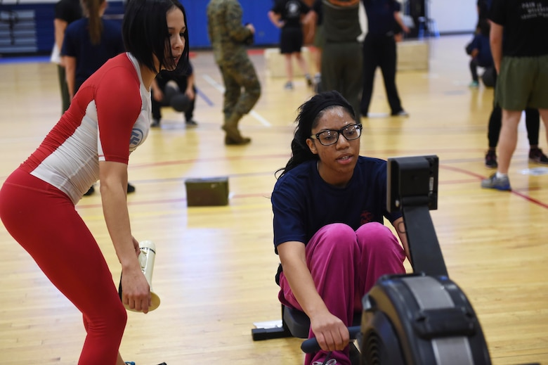 A U.S. Marine Corps poolee uses a row machine while Azul Farerra, 460th Force Support Squadron recreation assistant, instructs during a delayed entry program all-female workout held Jan. 17, 2015, at the fitness center on Buckley Air Force Base, Colo. Poolees are members of the DEP that have not yet shipped out to recruit training. The DEP workouts consist of strengthening exercises such as pull-ups, box jumps, push-ups and squats to enable poolees to be accustomed to the intense workouts and high-stress they will endure during recruit training. (U.S. Air Force photo by Airman 1st Class Samantha Saulsbury/Released)
