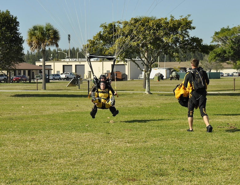 Sgt. 1st Class Jon Ewald, tandem instructor with the U.S. Army Parachute Team: The Golden Knights, and Maj. Brooke Cortez, 482nd Fighter Wing Public Affairs chief, prepare to land after a tandem jump at Homestead Air Reserve Base, Fla., on Jan. 29. The Golden Knights are conducting their sixth straight year of winter training at Homestead ARB. (U.S. Air Force photo/Tim Norton)