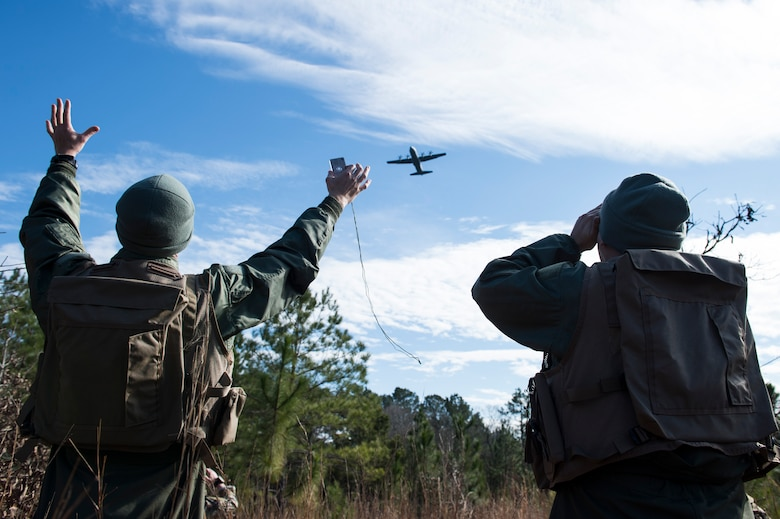 Airmen use signaling mirrors to communicate their location to a C-130J Super Hercules as it flies overhead Jan. 15, 2015, at Fort Polk, La. After signaling the aircraft, it dropped essentials for surviving in the wilderness such as Meals, Ready to Eat, water and communication equipment. The Airmen are assigned to Dyess Air Force Base, Texas. (U.S. Air Force photo/Senior Airman Cliffton Dolezal)