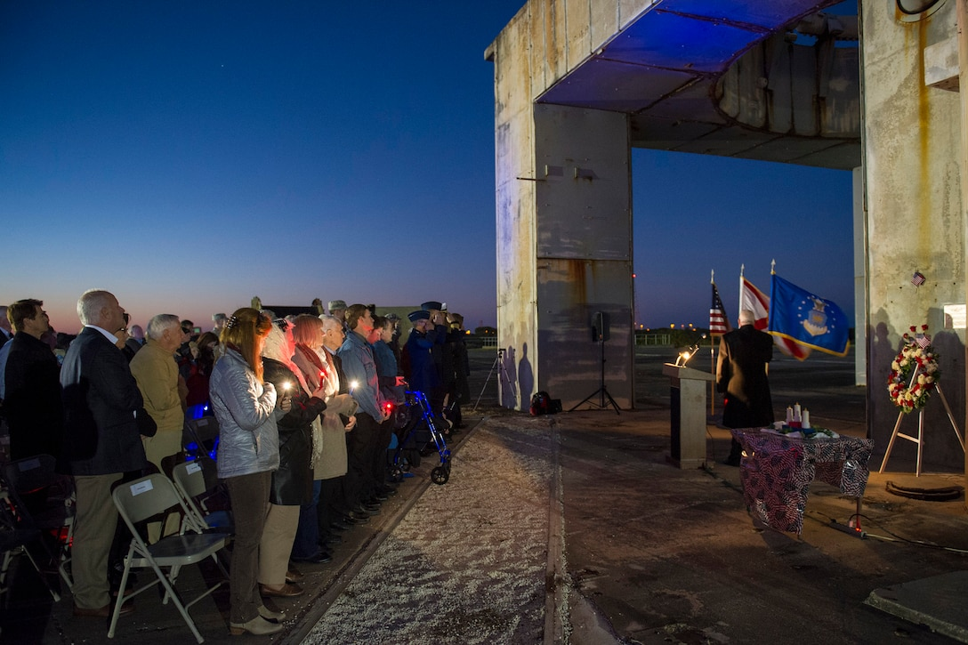 """Members of an audience honor three former space pioneers at the 48th annual Apollo 1 Memorial Ceremony Jan. 27, 2015, at Cape Canaveral Air Force Station, Fla. The ceremony honored the lives of the three crew members, Command Pilot Virgil """"Gus"""" Grissom, Senior Pilot Edward H. White II and Pilot Roger B. Chaffee, who were killed by a flash fire during a launch pad test of their Saturn 1B rocket, Jan. 27, 1967.  (U.S. Air Force photo/Matthew Jurgens)"""