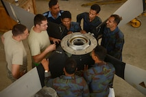 Tech. Sgt. Sam Bishop, center left, and Staff Sgt. Jeffrey Stephens discuss propeller maintenance with Bangladesh air force maintainers, from the 101st Special Flying Unit, during exercise Cope South 15 Jan. 27, 2015, at BAF Base Bangabandhu, Bangladesh. Bishop and Stephens are aerospace propulsion specialists assigned to the 374th Maintenance Group at Yokota Air Base, Japan. (U.S. Air Force photo/1st Lt. Jake Bailey)