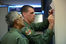 Lt. Col. Andrew Campbell, right, discusses a mission with Bangladesh air force Group Captain Awal Hossain during Cope South 15 Jan. 28, 2015, at BAF Base Bangabandhu, Bangladesh. Cope South is a Pacific Air Forces-sponsored, bilateral tactical airlift exercise conducted in Bangladesh, with a focus on cooperative flight operations, day and night low-level navigation, tactical airdrop, and air-land missions; as well as subject matter expert exchanges in the fields of operations, maintenance and rigging disciplines. Campbell is the 36th Airlift Squadron commander at Yokota Air Base, Japan. (U.S. Air Force photo/1st Lt. Jake Bailey)