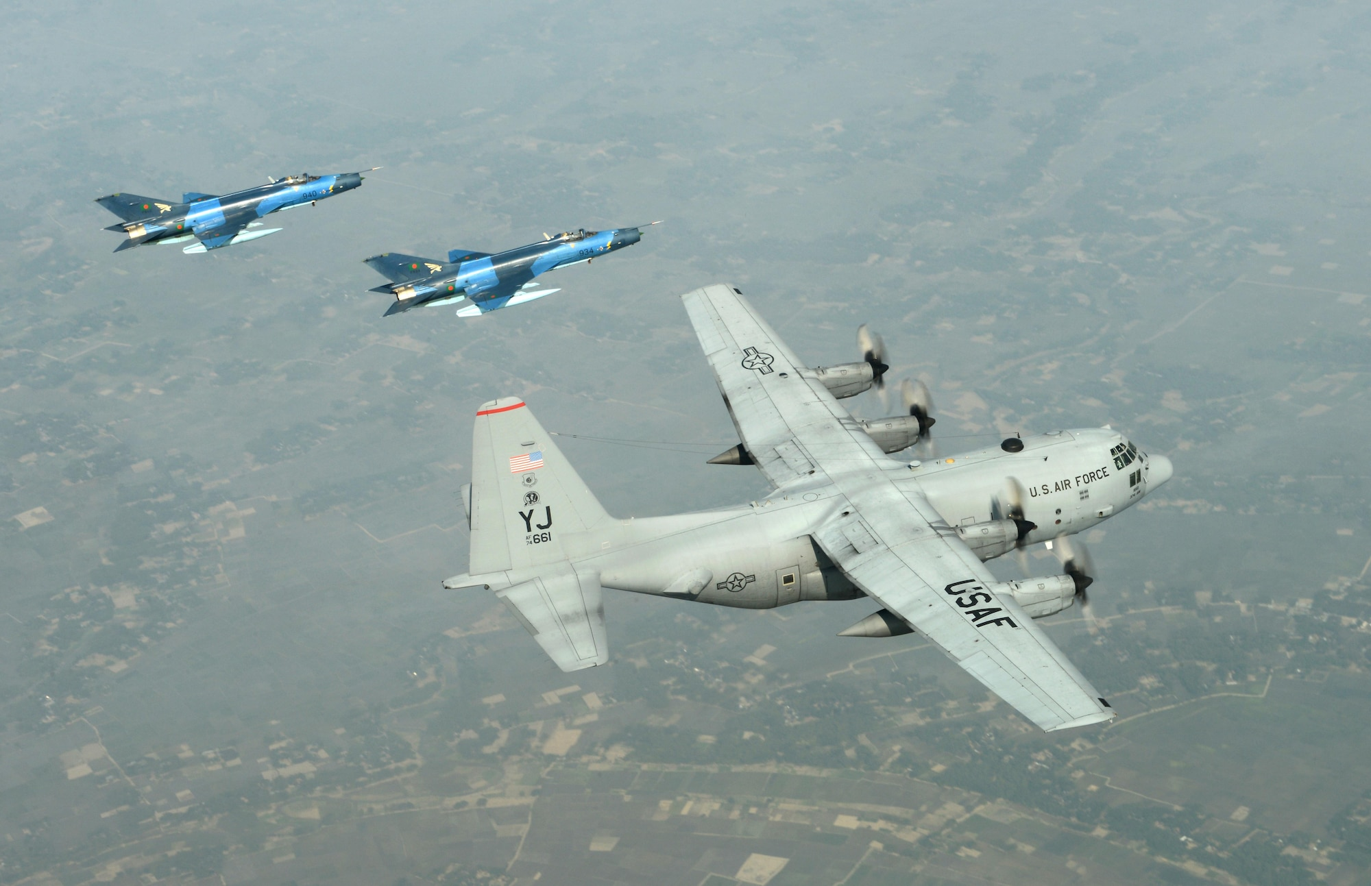 Two Bangladesh air force F-7BG Defenders escort a U.S. Air Force C-130H Hercules during Cope South 15 Jan. 28, 2015, near Kishoreganj, Bangladesh. Cope South is a Pacific Air Forces-sponsored, bilateral tactical airlift exercise conducted in Bangladesh, with a focus on cooperative flight operations, day and night low-level navigation, tactical airdrop, and air-land missions; as well as subject matter expert exchanges in the fields of operations, maintenance and rigging disciplines. The F-7Bs are assigned to the 5th Squadron at BAF Base Bangabandhu, Bangladesh. The C-130H is assigned to the 374th Airlift Wing at Yokota Air Base, Japan. (U.S. Air Force photo/1st Lt. Jake Bailey)