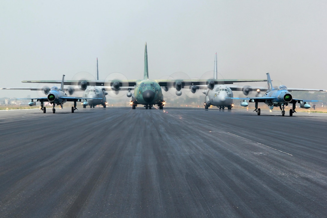 Two Bangladesh F-7BG Defenders, a BAF C-130B Hercules, and two U.S. Air Force C-130H Hercules aircraft prepare to take off Jan. 28, 2015, from BAF Base Bangabandhu, Bangladesh, during Cope South 15. The C-130H is assigned to the 374th Airlift Wing at Yokota Air base, Japan; the BAF F-7BGs are assigned to 5th Squadron and the BAF C-130B is assigned to 101st Special Flying Unit at BAF Base Bangabandhu, Bangladesh. (Courtesy photo/Bangladesh air force)