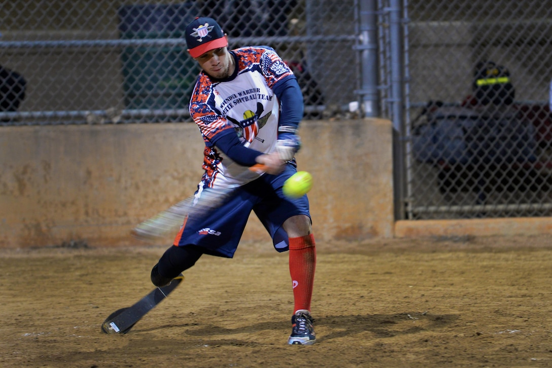 """Ryan """"Mac"""" McIntosh, Wounded Warrior Amputee Softball Team outfielder, connects with a pitch during the first game of a double header Jan. 24, 2015, in Southlake, Texas. The U.S. Army veteran lost part of his right leg below the knee while deployed in support of Operation Enduring Freedom. McIntosh stepped on a pressure plate land mine during a foot patrol two months into his first deployment Dec. 8, 2010. He currently travels the country with the WWAST, a group of veterans who sustained severe injuries resulting in amputation while serving in the military, and through extensive rehabilitation, they have become competitive athletes again (U.S. Air Force photo/Tech. Sgt. Mike Meares)"""