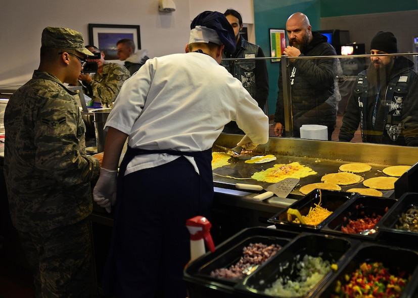 U.S. Air Force Air Commandos with the 27th Special Operations Force Support Squadron prepare breakfast for the Black Label Society in the Pecos Trail Dining Facility Jan. 28, 2015 at Cannon Air Force Base, N.M. The band was provided a tour of Cannon as part of a United Services Organization concert performed later that evening. (U.S. Air Force photo/Airman 1st Class Shelby Kay-Fantozzi)