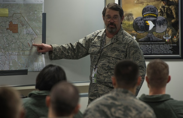 Bart Westfall, 34th Combat Training Squadron exercise planner assigned to Little Rock Air Force Base, Ark., briefs members of the 817th Contingency Response Group in a classroom before an exercise at the Joint Readiness Training Center at Fort Polk, La., Jan. 14, 2015. JRTC is a 34 CTS exercise for the U.S. Army that improves unit readiness by providing realistic, stressful, joint and combined arms training across the full spectrum of conflict. The Airmen helped support the exercise, and also provided an opportunity for internal training. (U.S. Air Force photo/Staff Sgt. Gustavo Gonzalez/RELEASED)