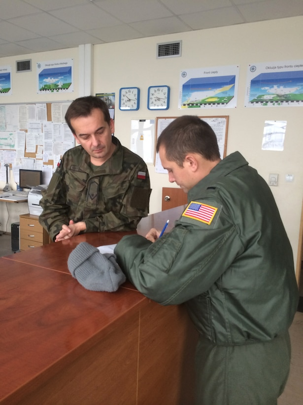 U.S. Air Force 2nd Lt. Tristan Stonger, a C-130 pilot for the Kentucky Air Guard's 165th Airlift Squadron, talks with a Polish Air Force official at Powidz Air Base, Poland, Dec. 10, 2014, during a three-week deployment in support of Operation Atlantic Resolve. The Kentucky Air Guard fielded two C-130 aircraft and 50 personnel to conduct joint training and focus on interoperability in support of NATO operations. (Courtesy Photo)