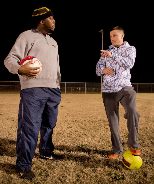 U.S. Air Force Master Sgt. Jason Butts, right, a ground explosives safety craftsman with the 116th Air Control Wing, Georgia Air National Guard, speaks to co-coach, Chris Harris, about game strategy during a practice held in Warner Robins, Ga., Dec. 9, 2014. Butts topped thousands of fellow coaches from 12 states to take the honor as the Region 3 Boys Recreational Soccer Coach of the Year for a team he coaches in Warner Robins, Georgia.  He also won the top spot as coach of the year for the state of Georgia, and his team has won three-consecutive state championships. Butts has served as a soccer coach in his community during his off-duty hours for the past seven years. (U.S. Air National Guard photo by Master Sgt. Roger Parsons/Released)