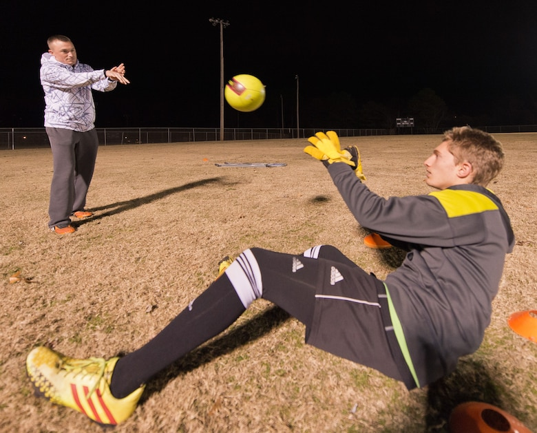 U.S. Air Force Master Sgt. Jason Butts, left, a ground explosives safety craftsman with the 116th Air Control Wing, Georgia Air National Guard, tosses a soccer ball to one of the players he coaches during a practice held in Warner Robins, Ga., Dec. 9, 2014. Butts topped thousands of fellow coaches from 12 states to take the honor as the Region 3 Boys Recreational Soccer Coach of the Year for a team he coaches in Warner Robins, Georgia.  He also won the top spot as coach of the year for the state of Georgia, and his team has won three-consecutive state championships. Butts has served as a soccer coach in his community during his off-duty hours for the past seven years. (U.S. Air National Guard photo by Master Sgt. Roger Parsons/Released)