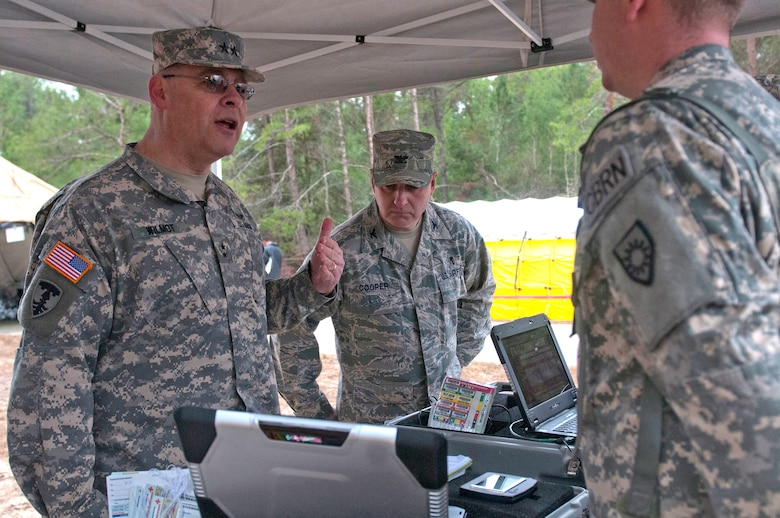 Army Maj. Gen. David E. Wilmot (left), deputy surgeon general for the Army National Guard, discusses the Emergency Tracking and Accountability System that Army Spec. Robert Schwallie (right) of the Kentucky National Guard CERFP is using to track casualties as they move from the hot zone into the cold zone during Operation Starke Thunder at Camp Blanding in Starke, Fla., Jan. 14, 2015. The four-day exercise certified the joint Kentucky Army and Air Guard emergency-response team as mission-ready. (U.S. Air National Guard photo by Staff Sgt. Vicky Spesard)