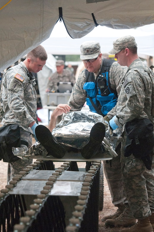 Soldiers from the Kentucky National Guard CERFP move a simulated patient from the hot zone into the cold zone for further triage as part of Operation Starke Thunder at Camp Blanding in Starke, Fla., Jan. 13, 2015. Non-ambulatory patients were moved through decontamination using a gurney placed on rollers. (U.S. Air National Guard photo by Staff Sgt. Vicky Spesard)