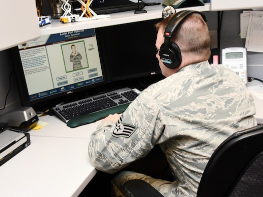 Staff Sgt. Gregory Schmidt, 423rd Mobility Training Squadron Logistics Transportation instructor, sits at a computer to demonstrate taking one of the many online training courses offered to Department of Defense members by the U.S. Air Force Expeditionary Operations School on Jan. 29.(U.S. Air Force photo/ Danielle Brooks)