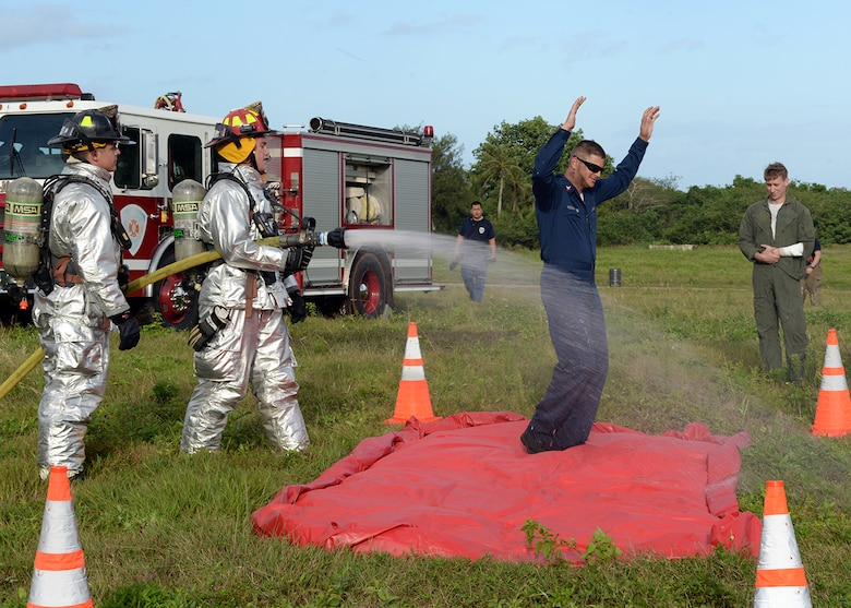 Andersen fire fighters simulate spraying hazardous chemicals off of a role player during a joint emergency management exercise Jan. 27, 2014, at Andersen South, Guam. During the EME, Guam and Andersen first responders were tested on how well they can work together to respond to various emergency scenarios on and off base. (U.S. Air Force photo by Senior Airman Cierra Presentado/Released)
