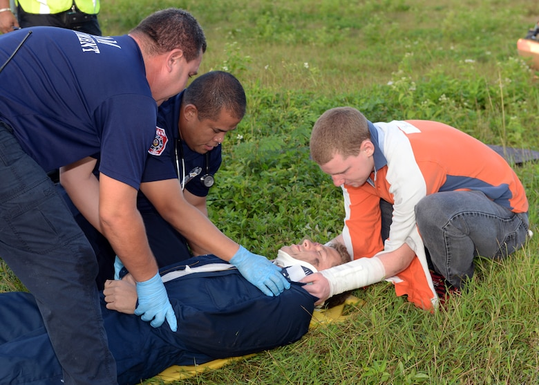 Andersen Airmen and Guam fire department emergency medical technicians stabilize a patient after a simulated helicopter crash during a joint emergency management exercise Jan. 27, 2014, at Andersen South, Guam. The exercise tested the island's ability to respond to a variety of emergencies and coordinate efforts amongst local and federal response organizations. (U.S. Air Force photo by Senior Airman Cierra Presentado/Released)