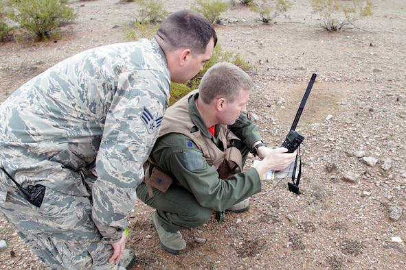 150130-Z-VA676-278 – Two Michigan Air National Guard Airmen practice using a rescue radio during a combat search and rescue exercise in the Barry M. Goldwater Air Force Range, west of Tucson, Ariz., Jan. 30, 2015. The 107th Fighter Squadron and related elements of the 127th Wing are participating in a series of training exercises known as Snowbird, while at the Total Force Training Center at Davis-Monthan Air Force Base. The 107th flies the A-10 Thunderbolt II and is assigned to Selfridge Air National Guard Base, Mich. (U.S. Air National Guard photo by Tech. Sgt. Dan Heaton)