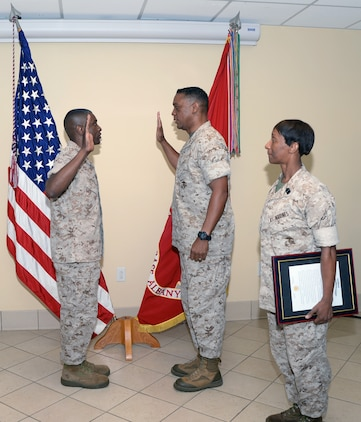 Col. James C. Carroll III, commanding officer, Marine Corps Logistics Base Albany, (left) recites the oath of office administered by Maj. Gen. Craig C. Crenshaw, commanding general, Marine Corps Logistics Command, as Sgt. Maj. Stephanie K. Murphy, sergeant major, LOGCOM, looks on during his promotion ceremony, July 1, at LOGCOM.