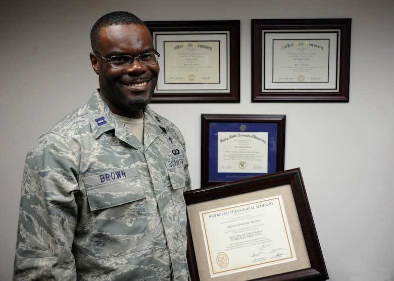 Captain Aleck Brown, 30th Space Wing chaplain, poses with his various collegiate diplomas, June 29, 2015, Vandenberg Air Force Base, Calif. Brown recently obtained his Doctorate in Philosophy of Biblical Teaching from Newburgh Theological Seminary. (U.S. Air Force photo by Airman 1st Class Robert J. Volio/Released)