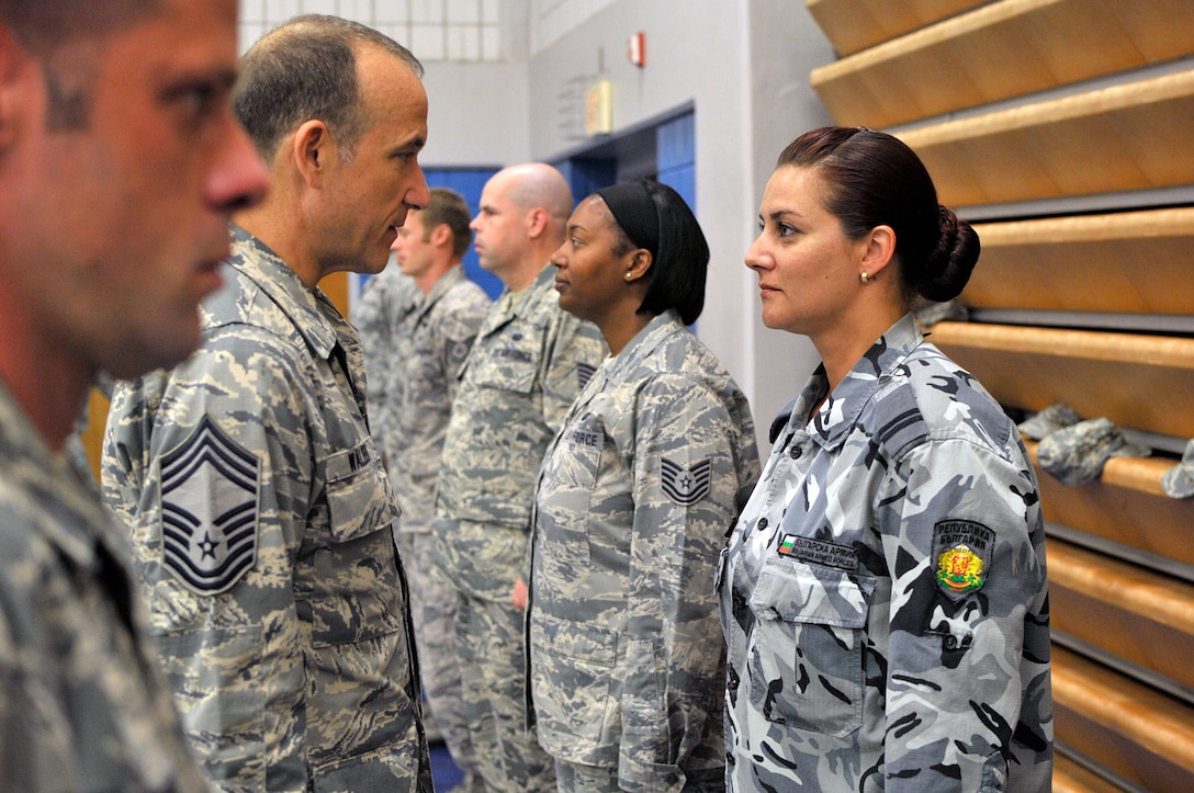 MCGHEE TYSON AIR NATIONAL GUARD BASE, Tenn. - Chief Master Sgt. Edward Walden, Sr., commandant of the Paul H. Lankford Enlisted PME Center, inspects the uniform of Bulgarian Staff Sgt. Bistra Koleva Kumanova here, June 23, 2015, during a uniform inspection in NCO academy. The EPME center hosts international military students from Bulgaria as well as from Canada and Jordan. (U.S. Air National Guard photo by Master Sgt. Mike R. Smith/Released)