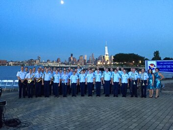 The Air National Guard Band of the Northeast takes the opportunity to take a group photo in Sinatra Park, Hoboken NJ on Monday June 29. The New York City skyline and the Freedom Tower are lit up for night in the background.