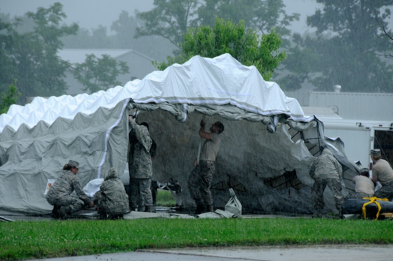 Members of the 182nd Airlift Wing's CERFP medical element erect a triage tent during a rainstorm at the Boone County Fire District Training Center on June 17, 2015, near Columbia, Mo. (U.S. Air National Guard photo by Tech, Sgt. Todd Pendleton)(Relased)