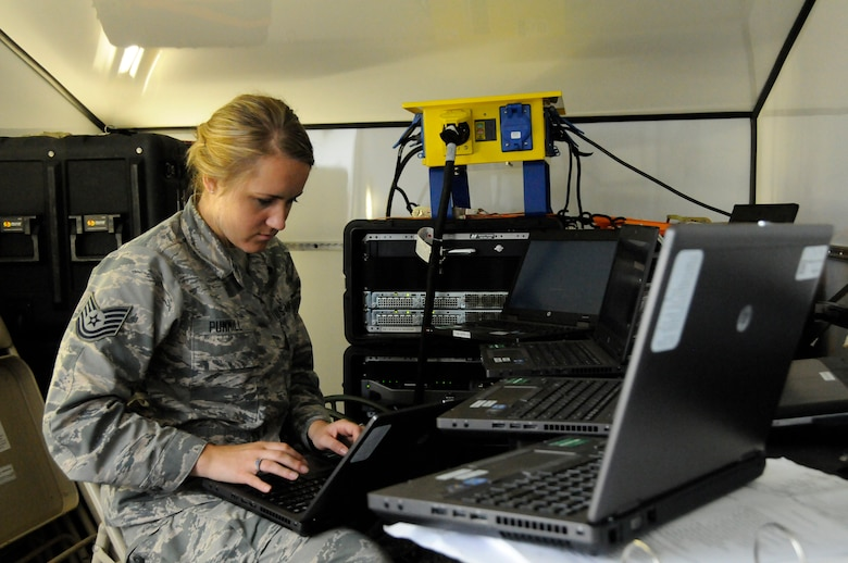 Tech. Sgt. Candace Pummill, a cyber systems operations specialist with the 264th Combat Communications Squadron, Peoria, Ill., configures a laptop computer for use inside the Joint Incident Site Communications Capability (JISCC) trailer June 16, 2015, at the Boone County Fire District Training Center near Columbia, Mo. (U.S. Air National Guard photo by Tech. Sgt. Todd Pendleton)(Released)