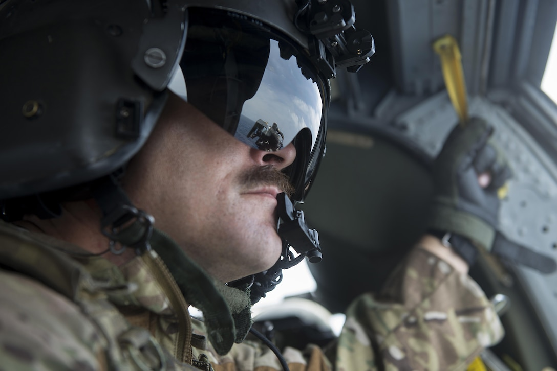 U.S. Air Force Master Sgt. Kenton Lewis, 33rd Rescue Squadron special missions aviator, looks out a window of a 33rd RQS HH-60G Pave Hawk helicopter during a large force exercise near Okinawa, Japan, June 30, 2015. During the exercise, numerous U.S. Air Force flying squadrons from Kadena Air Base, Japan, partnered with Vermont Air National Guard F-16 Fighting Falcons and U.S. Marine Corps units from Marine Corps Air Station on Okinawa in order to improve interservice interoperability in the region. (U.S. Air Force photo by Staff Sgt. Maeson L. Elleman)