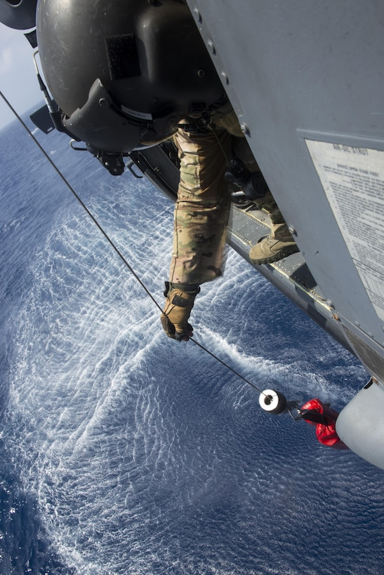 U.S. Air Force Master Sgt. Kenton Lewis, 33rd Rescue Squadron special missions aviator, simulates hoisting a casualty from the water using a winch aboard a 33rd RQS HH-60G Pave Hawk helicopter during a large force exercise near Okinawa, Japan, June 30, 2015. The exercise, which integrated U.S. Air Force and Marine Corps assets on Okinawa, was designed to allow the units to practice air-to-air capabilities while supporting ground troops. (U.S. Air Force photo by Staff Sgt. Maeson L. Elleman)