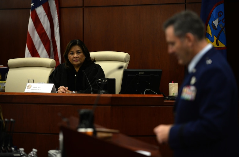 Frances Marie Tydingco-Gatewood, chief judge District Court of Guam, listens as Brig. Gen. Andrew Toth, 36th Wing commander, addresses newly naturalized U.S. citizens July 2, 2015, in Hagåtña, Guam. Twenty-four immigrants, originally from the Federated States of Micronesia, the Philippines, South Korea, Taiwan, Thailand and Vietnam, received their U.S. citizenship. (U.S. Air Force photo by Senior Airman Alexander W. Riedel/Released)