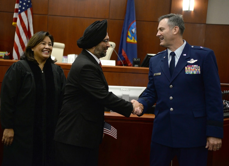 Brig. Gen. Andrew Toth, 36th Wing commander, right, congratulates Hargopal Sachdev, center, on his naturalization as U.S. citizen July 2, 2015, in Hagåtña, Guam. Toth welcomed 24 new citizens as Americans and encouraged them to value their individual heritage as they embrace their new home. (U.S. Air Force photo by Senior Airman Alexander W. Riedel/Released)