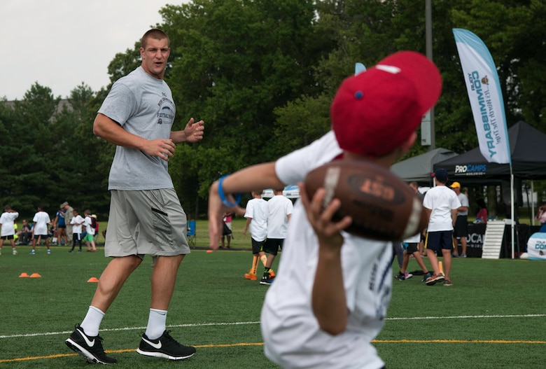 Rob Gronkowski, New England Patriots tight end, runs a route while a camper throws him a pass during a ProCamps event on Joint Base Andrews, Md., July 1, 2015. Gronkowski, a three time Pro Bowler and Super Bowl XLIX champion, coached approximately 100 kids during the two day camp. (U.S. Air Force photo/Airman 1st Class Philip Bryant)