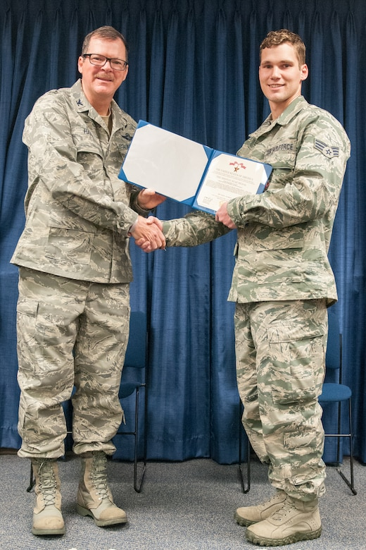 Col. Robert Hamm (left), commander of the 123rd Operations Group, presents the Bronze Star Medal to Senior Airman Robert Willging, a combat controller in the 123rd Special Tactics Squadron, during a ceremony at the Kentucky Air National Guard Base in Louisville, Ky., March 14, 2015. Willging earned the medal for his actions while deployed to Afghanistan. (U.S. Air National Guard photo by Staff Sgt. Vicky Spesard)