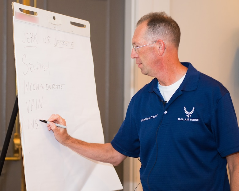 U.S. Air Force Maj. James Taylor, a chaplain and Strong Bonds instructor with the 116th Air Control Wing, Georgia Air National Guard, illustrates while teaching a class during the Strong Bonds singles retreat at the Sea Palms Resort, Saint Simons Island, Ga., June 26, 2015. The retreat, hosted by chaplains from the 116th Air Control wing, is a key component of the unit's resiliency program aimed at helping Airmen from Air National Guard units across Georgia to build relationships, learn to trust people, and hone their teambuilding skills. (U.S. Air National Guard photo by Senior Master Sgt. Roger Parsons/Released) (Portion of the photo blurred to removed name brand logo on presentation pad)