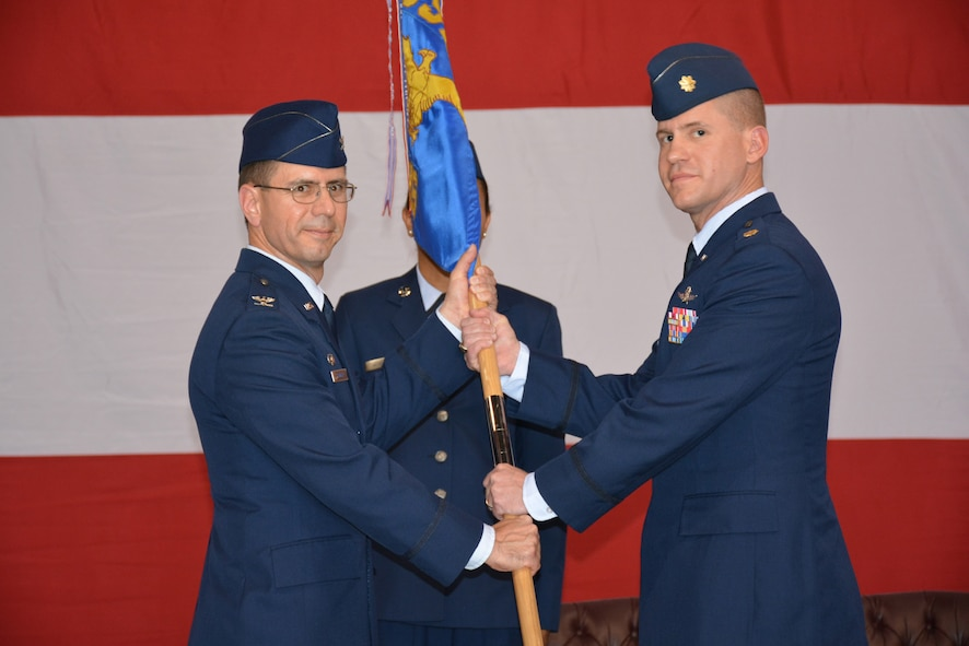 Col. Michael J. Homola, 552nd Air Control Group commander, left, passes the guidon to Maj. Victor R. Norris as the major assumes command of the 552nd Air Control Network Squadron during a ceremony June 26 in Bldg. 230. Major Norris replaces Lt. Col. Nicholas T. Kozdras, who is headed to Air Combat Command. Major Norris comes to Tinker Air Force Base having served as the lead cyberspace operations planner at North America Aerospace Defense Command and U.S. Northern Command. Colonel Homola presided over the ceremony. (Air Force photo by Darren D. Heusel/Released)