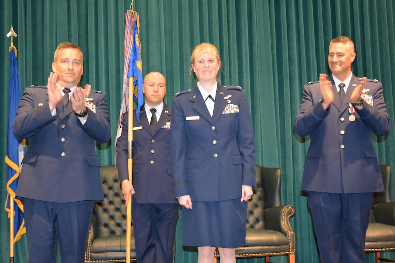Col. Alain Poisson, 552nd Operations Group commander, left, and Lt. Col. Keven Coyle, outgoing commander of the 960th Airborne Air Control Squadron, lead the congratulatory applause for Lt. Col. Kristen D. Thompson shortly after she assumed command of the squadron during a ceremony Tuesday in Fannin Hall. Holding the guidon is 1st Sgt. Anthony Sayers, 960th AACS. Colonel Poisson presided over the ceremony attended by approximately 100 family members, friends and co-workers. (Air Force photo by Darren D. Heusel/Released)