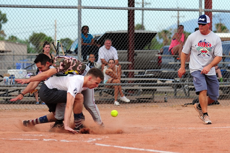 U.S. Air Force Master Sgt. Adam Boubede, 355th Civil Engineering Squadron electrical systems craftsman, collides with the 355th Equipment Maintenance Squadron's catcher during the Intramural Softball Championship game at Davis-Monthan Air Force Base Ariz., July 1, 2015. The 355th EMS began trailing 4-1, and then went on a run streak that put them ahead of the 355th CES 10-4, but lost in extra innings 13-12. (U.S. Air Force photo by Airman 1st Class Chris Drzazgowski/Released)