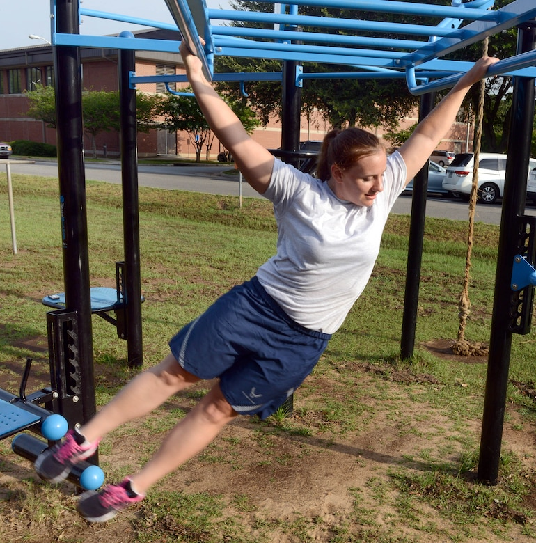 Capt. Kali Green, 5th Combat Communications Support Squadron flight commander, uses the monkey bars as a grip strength training tool.  Green recently competed in the television competition series American Ninja Warrior. (U.S. Air Force photo by Tommie Horton)