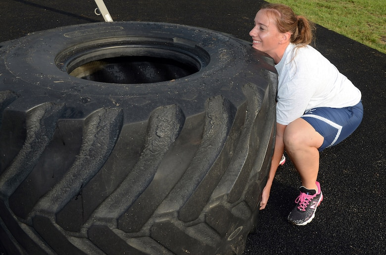 Capt. Kali Green, 5th Combat Communications Support Squadron flight commander, lifts a large tire as part of her training.  Green recently competed in the television competition series American Ninja Warrior. (U.S. Air Force photo by Tommie Horton)