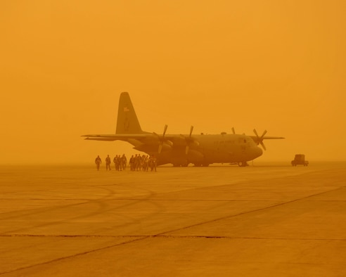 Passengers head back to the terminal to wait for a dust storm to lift at Sather Air Base, on the west side of Baghdad International Airport. Aircraft were grounded throughout the day as the dust brought visibility down to less than 1,000 meters. The passengers were brought to the aircraft in hopes that visibility would improve, however conditions deteriorated and stopped air travel around the Baghdad area. (U.S. Air Force photo by Master Sgt. Brian Davidson)