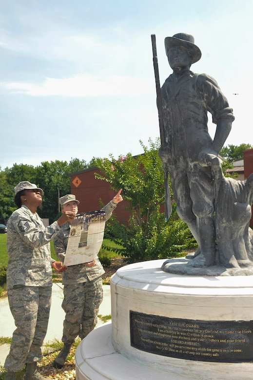 From right, Airman Samantha Grabowski and Master Sgt. Kathy Robinson, both members of the Air National Guard, refer to a brochure from the Minute Man National Historic Park as they look at the replica statue in front of the 116th Air Control Wing headquarters building. (U.S. Air Force photo by Misuzu Allen)