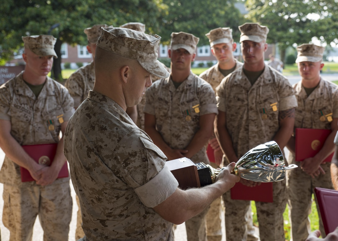 Lieutenant Col. Eric A. Reid, the commanding officer of 1st Battalion, 2nd Marine Regiment, speaks to his Marines about their incredible accomplishment while holding the Infantry Rifle Squad Competition trophy presented to his Marines during an award ceremony aboard Camp Lejeune, N.C., July 1, 2015. The squad from Alpha Company was declared the best rifle squad in the 2nd Marine Division after competing in the Infantry Rifle Squad Competition, a three-day physical and mental challenge that pushed the Marines to their limits and tested their abilities to work together as a cohesive unit. (U.S. Marine Corps photo by Cpl. Michelle Reif/Released)