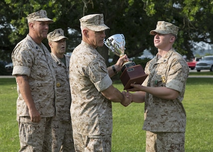 Major Gen. Brian D. Beaudreault, the commanding general of 2nd Marine Division, awards the Rifle Squad Competition trophy to Sgt. Jaymes L. Chambless, the squad leader of the winning squad from Alpha Company, 1st Battalion, 2nd Marine Regiment during an award ceremony aboard Camp Lejeune, N.C., July 1, 2015. The squad was declared the best rifle squad in the 2nd Marine Division after competing in the Infantry Rifle Squad Competition, a three-day physical and mental challenge that pushed the Marines to their limits and tested their abilities to work together as a cohesive unit. (U.S. Marine Corps photo by Cpl. Michelle Reif/Released)