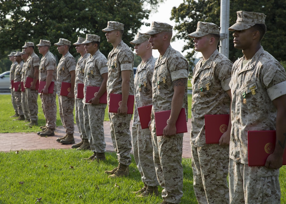 The winning rifle squad from Alpha Company, 1st Battalion, 2nd Marine Regiment, stands to receive applause after being pinned with a Navy and Marine Corps Achievement Medal and the Infantry Rifle Squad Competition Medal during an award ceremony aboard Camp Lejeune, N.C., July 1, 2015. The squad was declared the best rifle squad in the 2nd Marine Division after competing in the Infantry Rifle Squad Competition, a three-day physical and mental challenge that pushed the Marines to their limits and tested their abilities to work together as a cohesive unit. (U.S. Marine Corps photo by Cpl. Michelle Reif/Released)