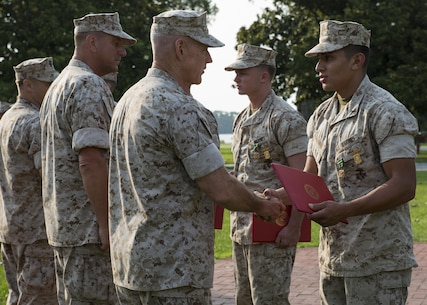 Major Gen. Brian D. Beaudreault, the commanding general of 2nd Marine Division, awards a member of Alpha Company, 1st Battalion, 2nd Marine Regiment a Navy and Marine Corps Achievement Medal and the Infantry Rifle Squad Competition Medal during an award ceremony aboard Camp Lejeune, N.C., July 1, 2015. The squad was declared the best rifle squad in the 2nd Marine Division after competing in the Infantry Rifle Squad Competition, a three-day physical and mental challenge that pushed the Marines to their limits and tested their abilities to work together as a cohesive unit. (U.S. Marine Corps photo by Cpl. Michelle Reif/Released)