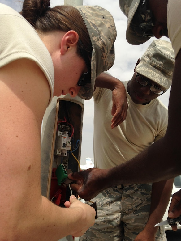 1st Lt Tawny Gardner, 379th Air Expeditionary Wing Sexual Assault Response Coordinator, re-wires a street light with SrA Dominic Jordan and